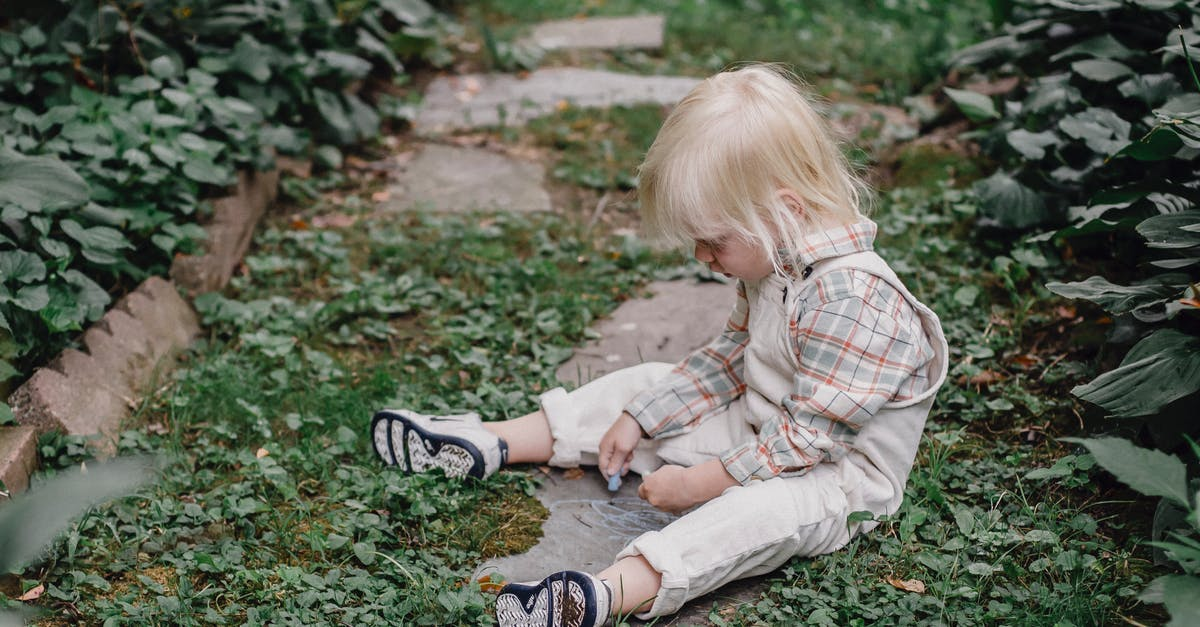 A little boy that is sitting in the grass